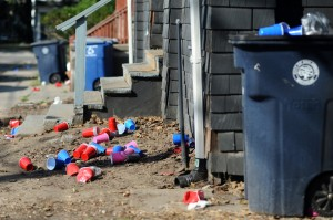 Plastic cups and trash litter the yards and sidewalks of house along Greenwood Ave. on Friday morning.